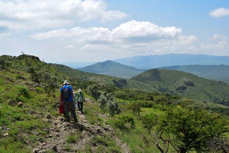 A rear view of hikers against mountains, Oloroka Mountain Range, Kenya Stock Photo