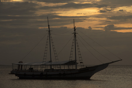 oceana: Ship silhouette over the sea against the light at sunset