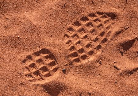 treads: shoe footprint on reddish sand in strong sunlight