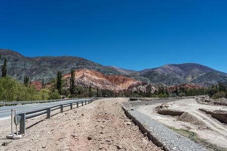 siete: Cerro de siete colores (hill of the seven colors)  in Purmamarca, Quebrada de Humahuaca,  Jujuy, Argentina. River, road and guardrail