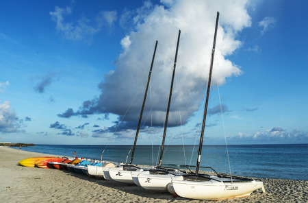 furled: Sailboat stranded on the beach of Varadero with furled sails. Sea and clouds as background