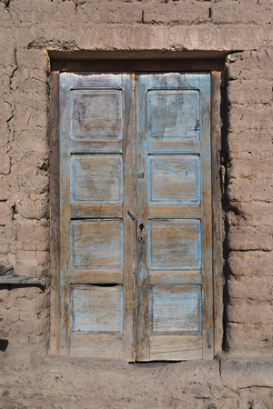 adobe wall: Old painted blue door on adobe wall