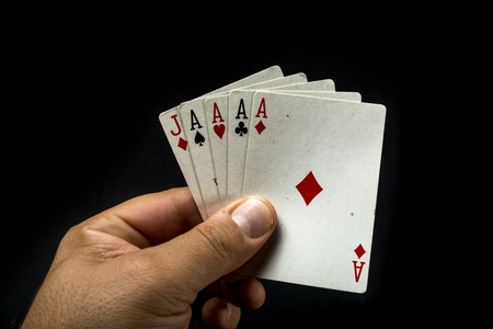 aces: Hand holding poker cards to form a aces poker on black background