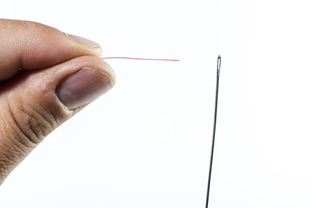 hand of man threading a needle with red thread on white background Stock Photo