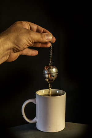 mans hand preparing tea in a bowl with infuser, on background Stock Photo
