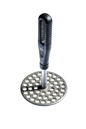 stainless steel: Metal masher potato with black plastic handle, over white background Stock Photo