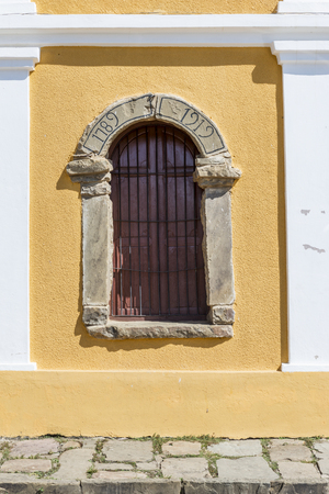 Window with arch with stone frame and fence on yellow wall. Says 1789 - 1912