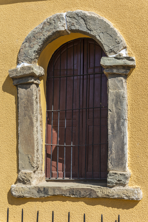 Window with arch with stone frame and fence on yellow wall