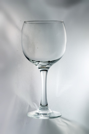four objects: Empty glass cup on white or light gray background Stock Photo