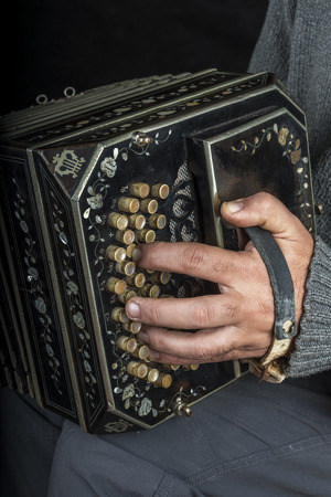 bandoneon: Musician playing a very old bandoneon, you only see the the left hand and the instrument