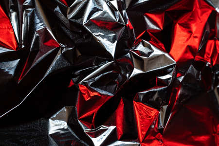 Crumpled aluminum foil, red neon glare on metal surface