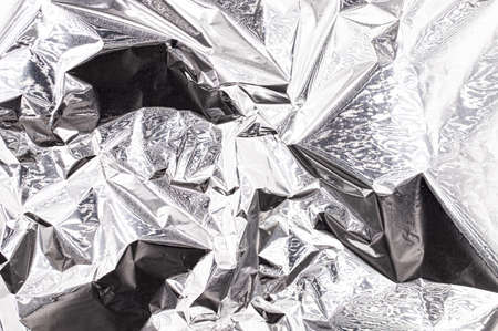 Crumpled metallic silver foil, shiny aluminum surface, abstract background