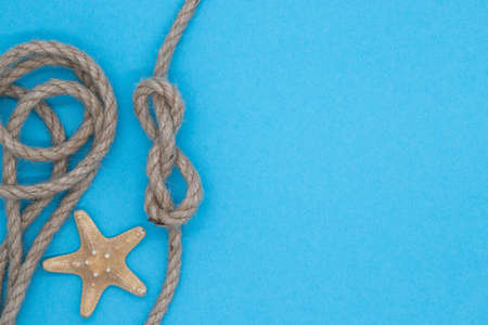 Starfish and rope on a blue bright background, summer nautical pattern
