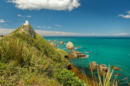 New Zealand - Nugget point on Southern Island, one of the most iconic landforms on the Otago coast, at the northern end of the Catlins coast, road from Kaka Point, lighthouse, rocky islets-The Nuggets