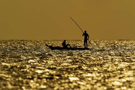 Zanzibar Island coast (Tanzania, Zanzibar Archipelago). Typical local aboriginal boats in the evenind and the dusk. Ocean with the sailing boat. Sunrise or sunset, silhouette and outline.