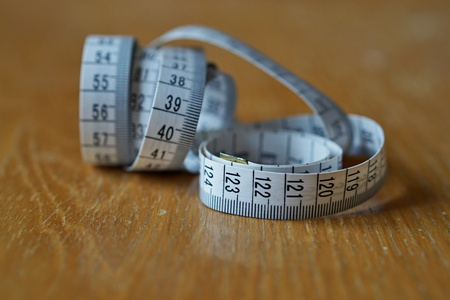 lose up: Tape measure (measuring length in centimeters and meters, Frequently Used for measuring the perimeter of human body During the diet) on the wooden surface