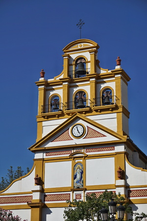 Top of the church in the town of La Linea de la Concepcion in southern Spain as a typical Spanish bell tower, a symbol of Spanish religious architecture and design