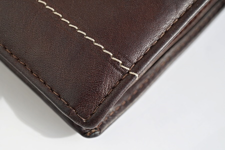Macro detail of a white and brown thread stitching black and brown stitched leather wallet Stock Photo