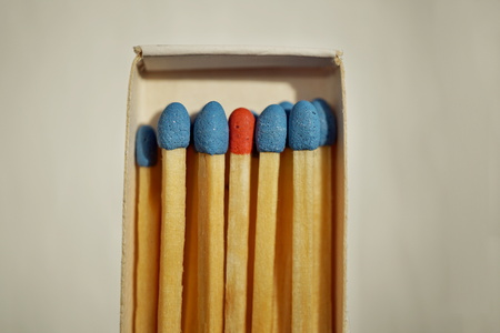 dissimilarity: Macro detail of a box of matches (matchbox) full of matches with blue top and one different with a red top as a symbol of difference, differentness and dissimilarity Stock Photo