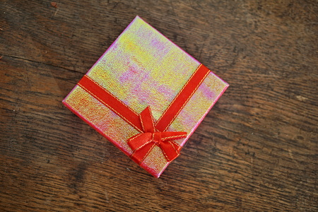 to get warm: Closed pink gift box with red ribbon and golden stitching on the wooden background as a symbol of giving and getting beautiful presents