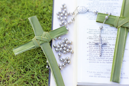 palm sunday: palm crosses with rosary beads and a bible Stock Photo