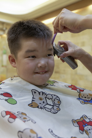 7 year old: a 7 year old mixed race boy getting a hair cut