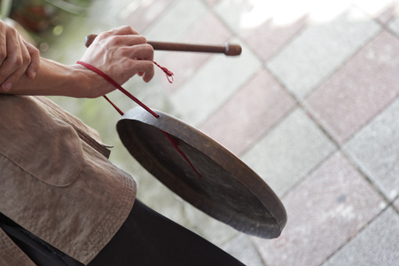 a mans hand beating a tin drum at a ceremony