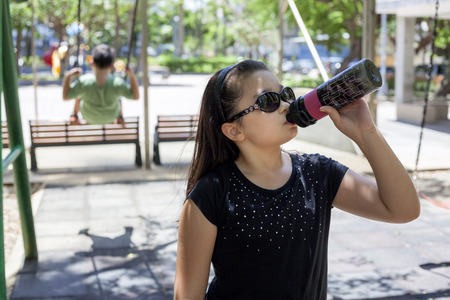 mixed race girl: young mixed race girl drinking to cool down in the park Stock Photo