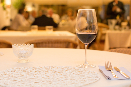 table with glass of wine in restaurant with many people