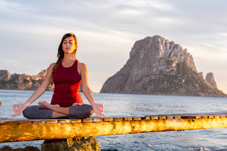 Es vedra, Ibiza : 2015 April 19 : Attractive woman practice yoga at beach with sunset or sunrise in Es Vedra, Ibiza, Spain.