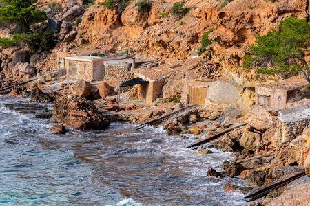 Cala Salada and Saladeta in san Antonio Abad at Balearic Islands Spain. Typical house for fishing boats and rocks. Фото со стока