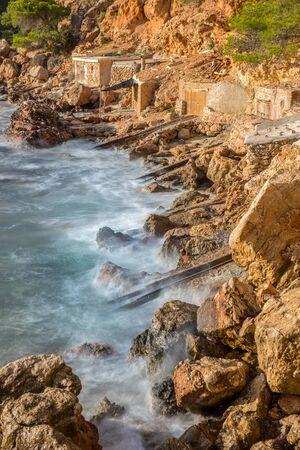 Cala Salada and Saladeta in san Antonio Abad at Balearic Islands Spain. Long exposure, Typical house for fishing boats and rocks.