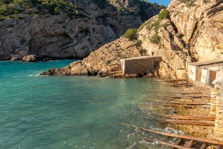 Turquoise waters in Es Portitxol, Ibiza, Spain. Hidden bay on the Island of Ibiza, in Sant Joan de Labritja. Imagens