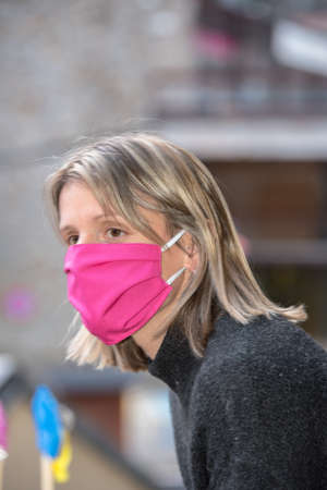 Blonde woman with face mask worried about the Covid-19 outbreak staying at home. Editorial