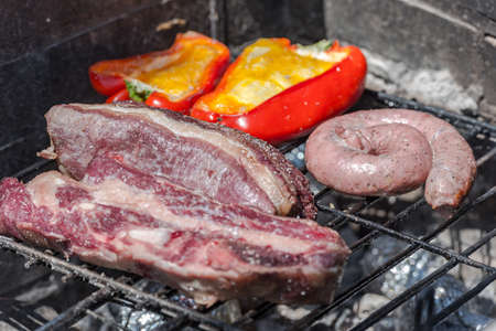Closeup take of a traditional Argentinian and Uruguayan barbecue, Creole sausage, whit peppers and eggs. Stock fotó