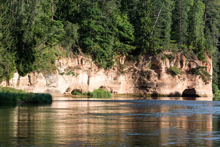 river with reflections in weater and sandstone cliffs in latvia