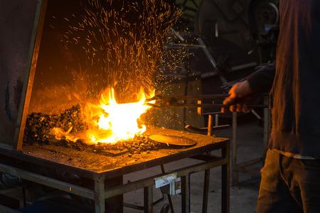 De smid die vlammen in smidse met vonk vuurwerk Stockfoto