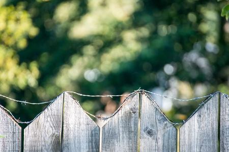 rusty nail: old wooden fence with barbed wire on top Stock Photo