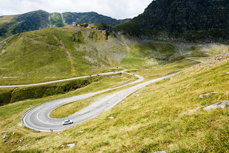 View to the carpathian mountains war road transfagarasan from the top with lonely trees and clouds above Stock Photo