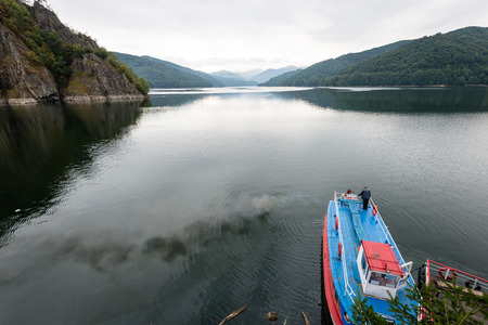 Reflections in the calm lake water with dramatic clouds with small boat Stock Photo