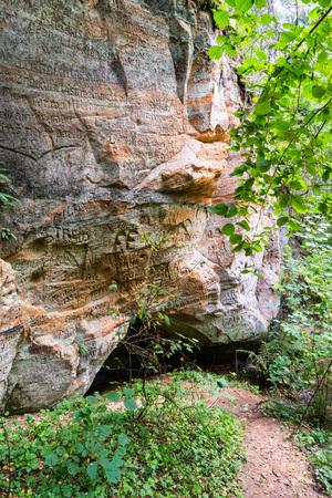 sandstone cliffs with inscriptions near tourist trails