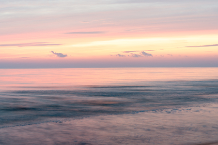 dramatic blue sunset with washed out waves with long exposure