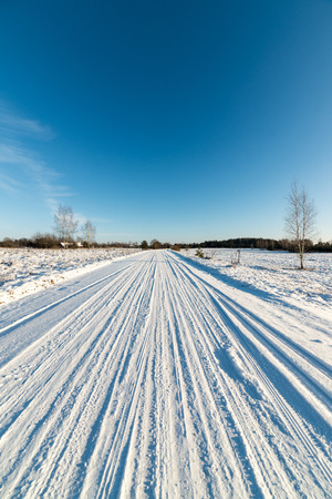 snowy field: snowy winter road with tire markings and blue sky Stock Photo