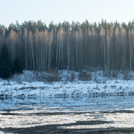 beautiful snowy winter landscape with frozen river and blue sky Stock Photo