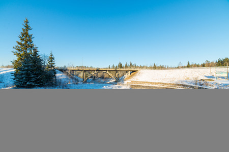 snowy winter river landscape with metal bridge and blue sky Stock Photo