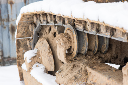 Detail of caterpillar track in construction site with dust and snow