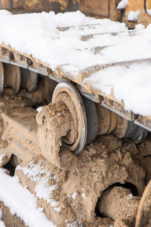 heavy snow: Detail of caterpillar track in construction site with dust and snow