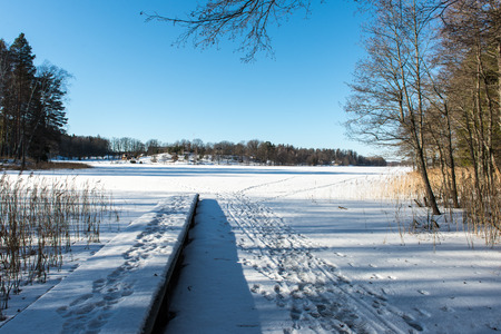 snowy field: frozen lake in winter with boardwalk and ice blocks. Gauja National Park. Latvia.