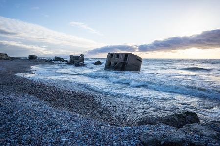 waves crushing over rocks and ruins of old fort at sunset on the beach Stock Photo