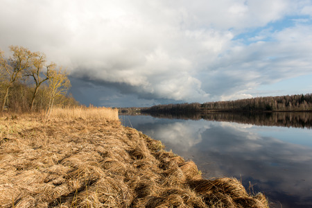 a situation alone: dramatic clouds over the river in misty morning in spring with reflections in water